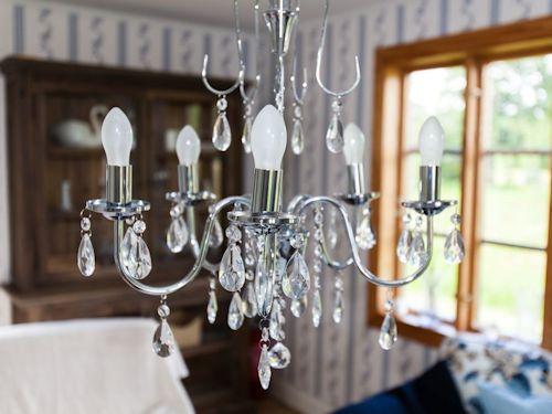 """Schweden Ferienhaus am See """"Torp Staveryd"""" - Details wie der Kronleuchter runten da harmonisch eingerichtet Wohnzimmer ab"""