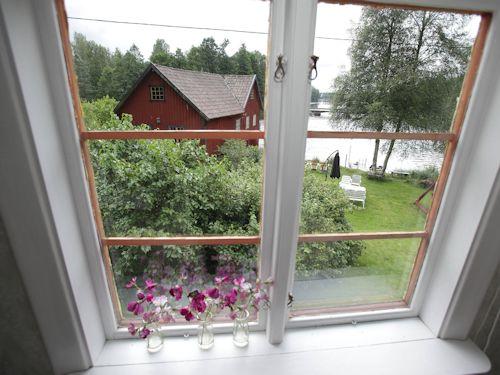 Blick aus dem Schlafzimmerfenster auf den Garten, die Mühle und den See Vrigstadsan.